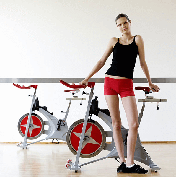A young woman standing next to an exercise bike