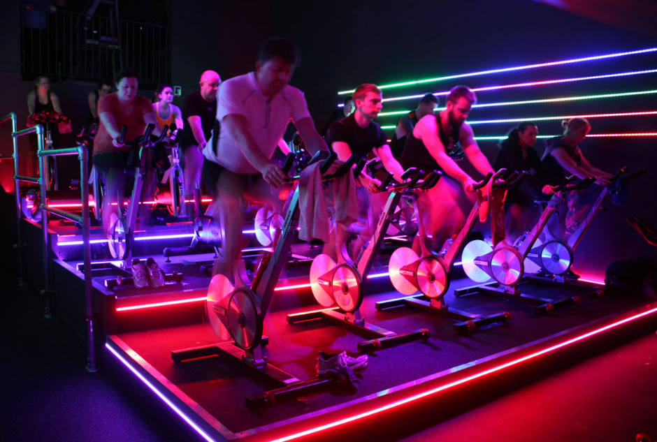 A simple lighting with LED strip should be enough to bring in ambient light for your workout